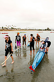 USA, California, San Diego, a group of women bring their boat in from the water after rowing around Vacation Isle, Mission Bay Park
