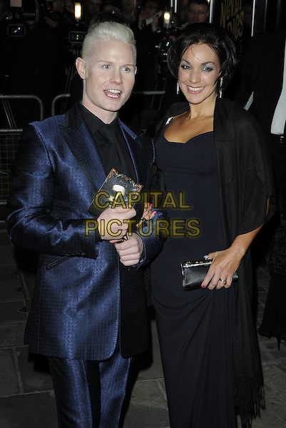 RHYDIAN ROBERTS & GUEST.The world premiere of 'Love Never Dies', Adelphi Theatre, London, England. .March 9th, 2010 .half 3/4 mouth open length black blue dress suit .CAP/CAN.©Can Nguyen/Capital Pictures.