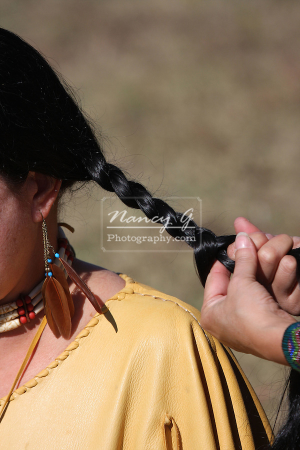Two Native American Indian women with fringe leather dress braiding eachother braids