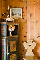 Close up of an 18th century painted Austrian corner cabinet against the wooden wall panelling of the living room