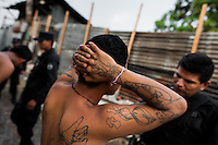 The Barrio 18 gang members are detained by the police officers from the special emergency unit (Halcones) in a gang neighbourhood of San Salvador, El Salvador, 13 May 2011. Although the murder rate in the country has dropped significantly, after a truce between two major street gangs (Mara Salvatrucha and Barrio 18) was agreed in 2012, the lack of security and violence are still the main issues in people's daily life. Due to the fact the gangs have never stopped their criminal activities (extortions, distribution of drugs and kidnappings), the Police anti-gang forces keep running their operations and chasing the 'homeboys' (how the gang's foot soldiers usually call themselves) in the poor, socially deprived suburbs of Salvadoran cities.