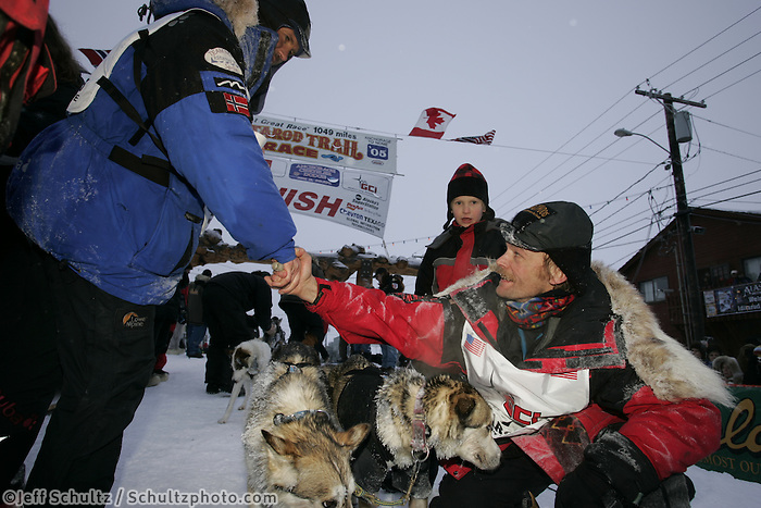 First place finisher Robert Sorlie (left) congratulates third place finisher Mitch Seavey at the finish line in Nome.  End of the  2005 Iditarod Trail Sled Dog Race.