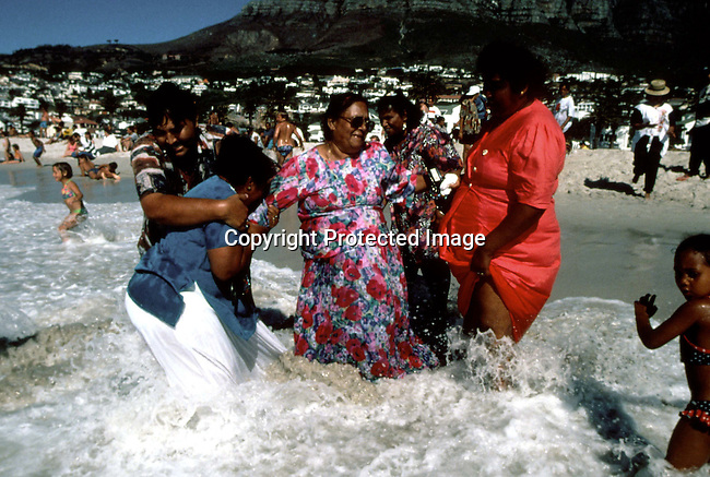 dipplei00061 .People leisure. Unidentified people on holiday on December 26, 1997 bathing at Camps Bay Beach, Cape Town South Africa. Camps Bay is one of the most affluent neigborhoods in Cape Town..©Per-Anders Pettersson/iAfrika Photos