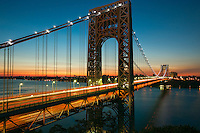 Morning rush hour traffic creates streaks of light on the George Washington Bridge as commuters cross the Hudson River between Fort Lee, New Jersey and Fort Washington, New York under a colorful sky just before sunrise on a summer morning.