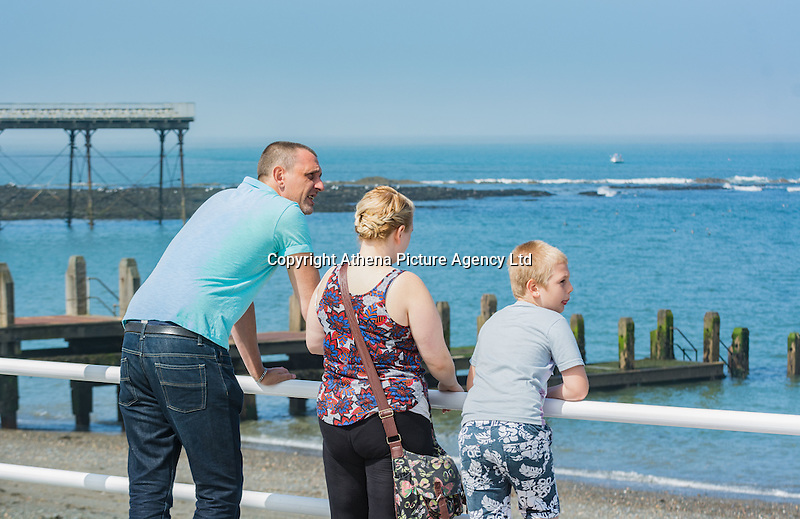 UK Weather: Aberystwyth, Ceredigion, West Wales Monday 18th July 2016. Holiday makers and locals alike take advantage of the early morning Sun to walk on the promenade and even enjoy an ice cream. The RNLI are out in force both making sure people are safe and raising awareness of the work they do.  Although it is overcast the sun is breaking through and the temperatures are expected to hit the low 20C with the mini heat wave expected to continue tomorrow reaching 30