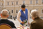 Couple dining at cafe table in Rome, Italy. Waiter serving drinks.