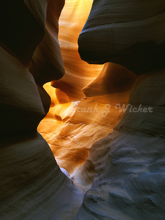 Golden light at the end of a sandstone tunnel in Lower Antelope Canyon near Page Arizona.  Navajo tribal park, LeChee Chapter