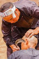 Asia,Cina,Guizhou,Basha,Traditional Basha hair shaving with a sickle on a man with a hair bun of the Basha minority ,China minority