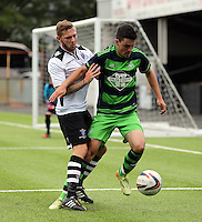 Pictured: Owain Jones of Swansea (R) challenged by a Merthyr Town player Saturday 11 July 2015<br />