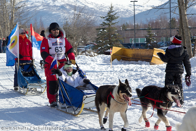 Mikhail Telpin and team run past spectators on the bike/ski trail during the Anchorage ceremonial start during the 2013 Iditarod race.    Photo by Britt Coon/IditarodPhotos.com