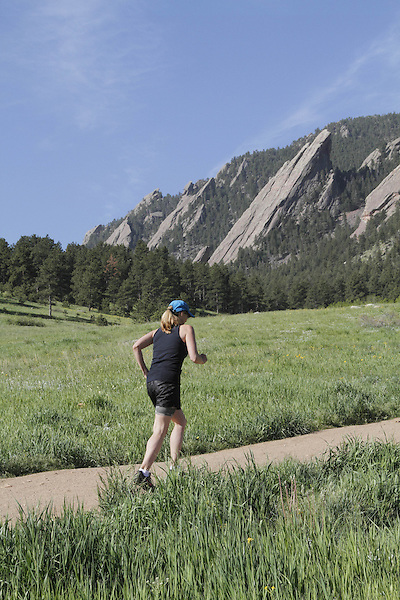 Woman trail running uphill at Chautauqua Park with the Flatirons rock formation behind, Boulder, Colorado, USA .  John leads private photo tours in Boulder and throughout Colorado. Year-round.