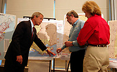 Washington, D.C. - September 4, 2005 -- United States President George W. Bush examines a map of shelters and kitchens in Louisiana during a visit to the American Red Cross Command Center in Washington, D.C., September 4, 2005. At right are Red Cross President and CEO Marty Evans (red shirt) and Executive Vice President, Chapter and International Operations, Alan McCurry.<br /> Credit: Martin H. Simon - Pool via CNP