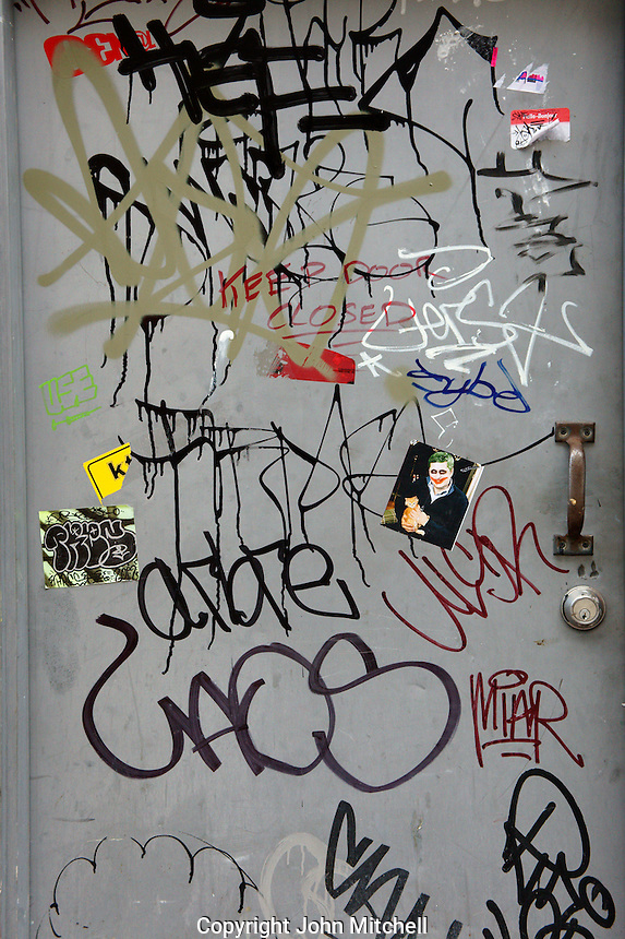 Metal door covered in urban grafitti, Vancouver, BC, Canada