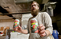 NWA Democrat-Gazette/DAVID GOTTSCHALK Andrew Blann, manager at Fossil Cove Brewery in Fayetteville, displays Tuesday, April 10, 2018, the new can for their Birch Ave. Blonde beer inside the new facility under renovation on Poplar Street. The expansion will move most of it's brewery operation to the new location about half a block away from the original location.