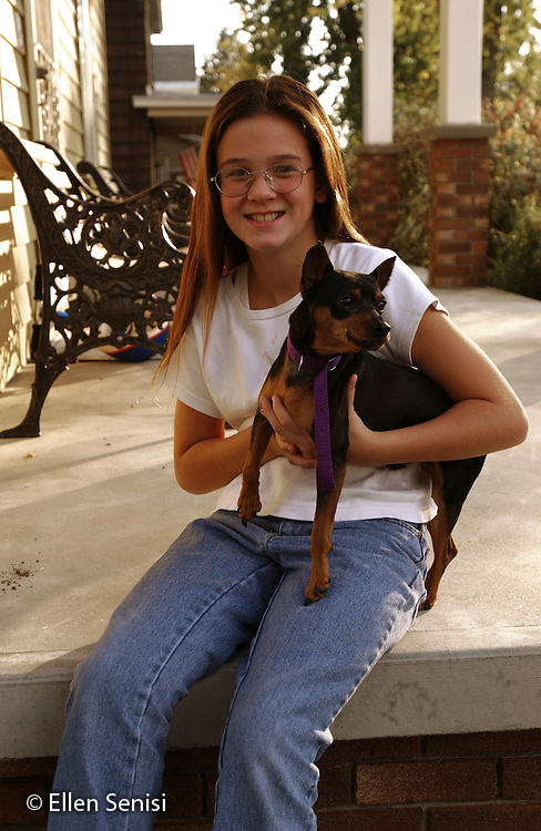 MR / Schenectady, NY.Girl (9) with family pet dog (miniature pinscher) at home..Vig1.©Ellen B. Senisi