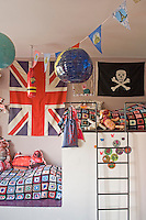 This child's bedroom has a raised bunk-style bed and is decorated with flags and bunting