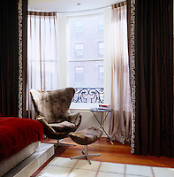 The open plan bedroom includes an Arne Jacobsen 'Egg' chair and footstool in the bay window