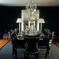 An atmosphere of elegent decadence has been created in the dining room of a London apartment with studded black leather dining chairs in a room of midnight blue