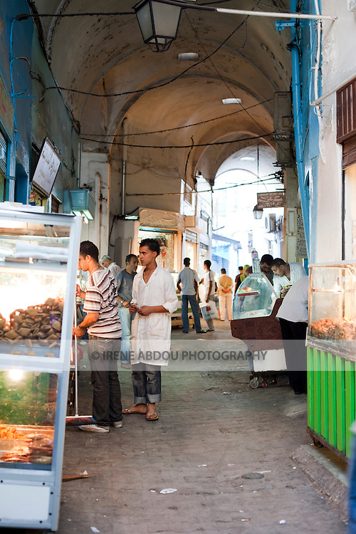 Shoppers stroll through the pastry section of the Medina (old city) Tunis, Tunisia.  Tunis's Medina is a UNESCO World Heritage Site.
