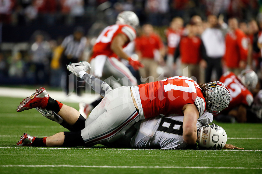 Ohio State Buckeyes defensive lineman Joey Bosa (97) hits Oregon Ducks quarterback Marcus Mariota (8) during the 4th quarter of the College Football Playoff National Championship at AT&T Stadium in Arlington, Texas on Jan. 12, 2015. (Adam Cairns / The Columbus Dispatch)
