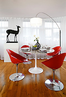 A contemporary dining room with a polished wood floor. The room is furnished with classic furniture including four Red Philippe Starck dining chairs and an Eero Saarinen white Tulip dining table. The deer bronze gives the room added weight.