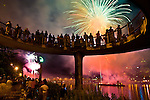 4th of July celebration .  FIreworks as seen from the East side of the river through a pedestrian walkway crowed with onlookers