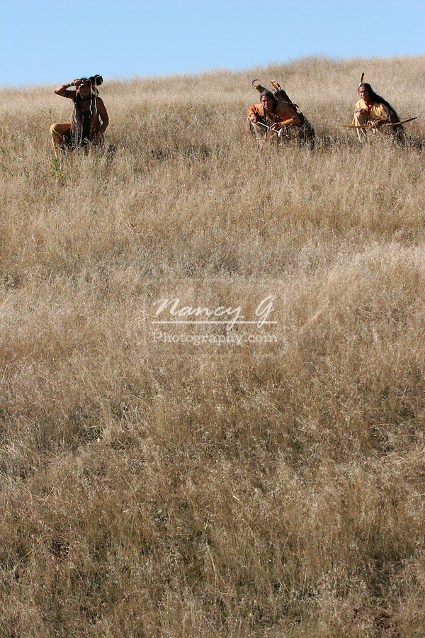 Three Native American Indian men crouching in the dead grasses hunting game or going into battle