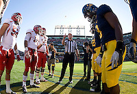 California and Utah captians watch referee Terry Leyden tosses a coin during coin toss ceremey before the game at AT&T Park in San Francisco, California on October 22, 2011.   California defeated Utah, 34-10.