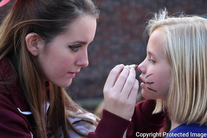 Weymouth High School cheerleader Mary Young paints Samantha Salmans face during the Thomas W. Hamilton Parent Council 7th annual Fall Festival Saturday October 25, 2014 at Thomas W. Hamilton Primary School in Weymouth.(Photo by Gary Wilcox)