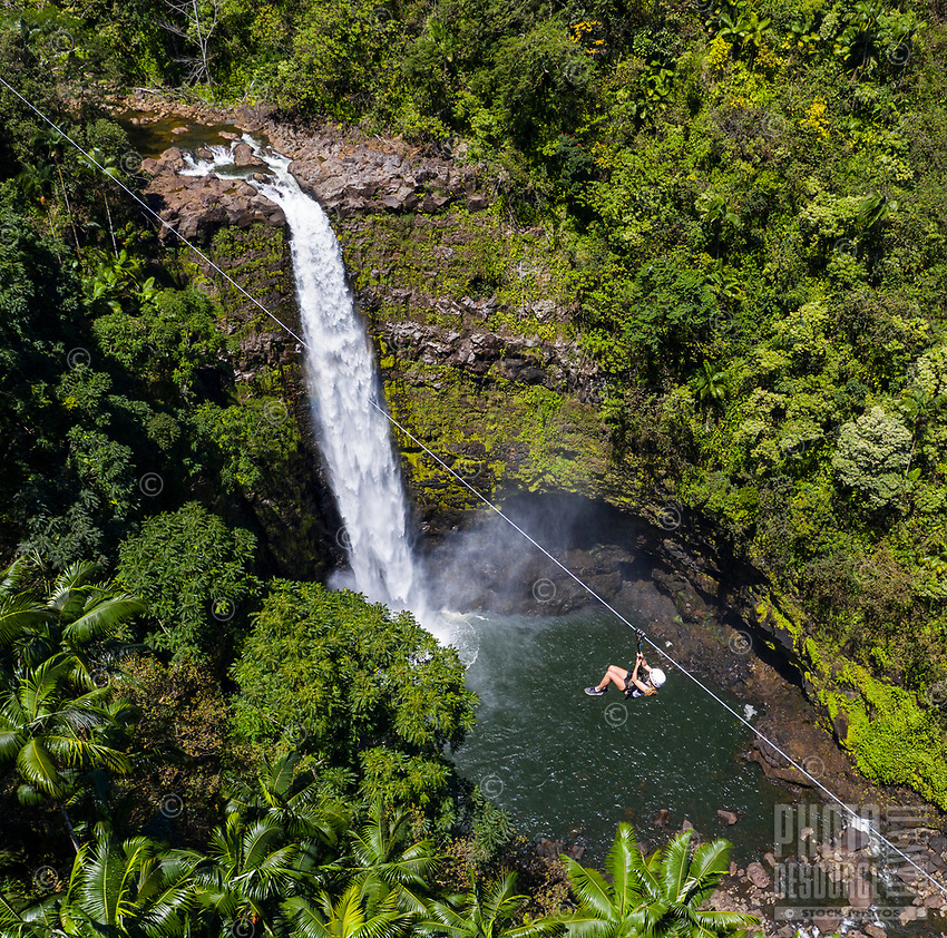 A woman ziplines past 'Akaka Iki Falls, Big Island of Hawai'i.