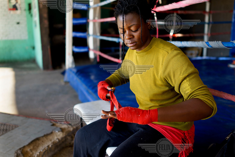 Selina Mabunda wrapping her knuckles before boxing training at the Hillbrow Boxing Club. After gunshot injuries put an end to his own boxing career, George Khosi founded the club to instil discipline, camaraderie and an activity away from the streets for young people from the community, and also to provide a training space for upcoming professional boxers. The club operates in a donated space on the forecourt of a disused petrol station in Hillbrow, one of the country's most notorious neighbourhoods.