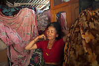 Tej Kumari Shrestha, 65, dresses her hair inside of her temporary house at Shila Porbot, outskirts of Kathmandu, Nepal. Tej Kumari Shrestha lost her home in last month's Nepal earthquake and now she lives in a temporary house in the bank of a river. May 8, 2015