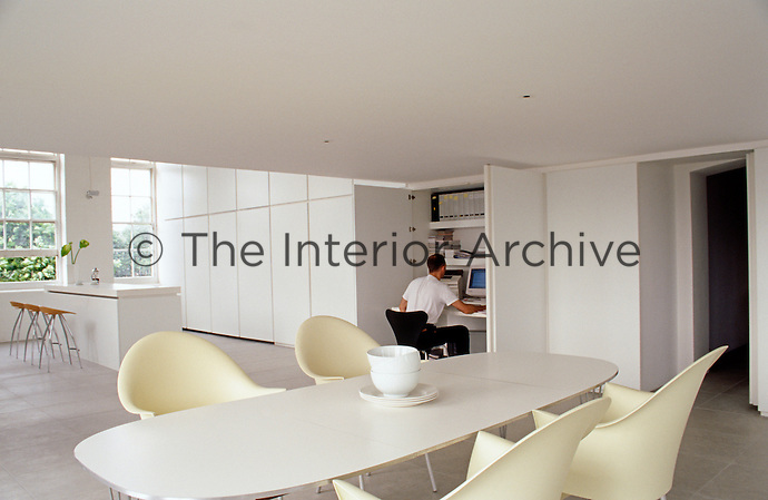 View over the white dining table towards the kitchen area with a man at work on his computer in one of the built-in cupboard units