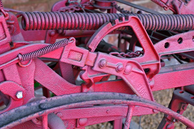 An up close look at the workings of an old tractor, painted fire-engine red, on display at The Farm on the grounds of the Biltmore Estate, Ashville, NC. The giant and small sprngs, chains, gears and top of the iron wheel create an interesting and intriquing image.