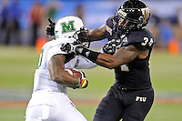 20 December 2011:  FIU linebacker Winston Fraser (34) tackles Marshall running back Travon Van (7) in the second quarter as the Marshall University Thundering Herd defeated the FIU Golden Panthers, 20-10, to win the Beef 'O'Brady's St. Petersburg Bowl at Tropicana Field in St. Petersburg, Florida.