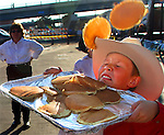 Cheyenne volunteer Jace Poulignot, 10, gets pelted with pancakes as tries to catch them during the free pancake breakfast at the Depot Plaza Monday morning.  Over 9025 people took advantage of the free breakfast. Michael Smith/WTE.