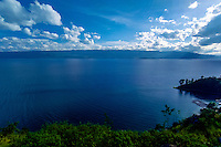 Indonesia, Sumatra. Toba. View of the Toba Lake from the mainland, Parapat side. It is blue, it is green, it is a travellers dream! The Tuk Tuk peninsula can be seen to the right in the photo, as a dark, small line in front of Samosir island. This is the main destination for most of the travellers that come here.