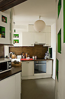 The alcoves and cupboards are the focus of this retro-style kitchen painted in white and lime green