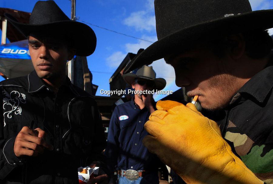 Young bull riders light up cigarettes to calm their nerves before the bull riding event at the 4th of July Makawao Rodeo which is held annually at the Oskie Rice Arena in Olinda, upcountry Maui. The rodeo is the largest rodeo in Hawaii, typically attracting more then 4000 spectators, and the prize money brings daring bull riders from Maui as well as neighboring islands.