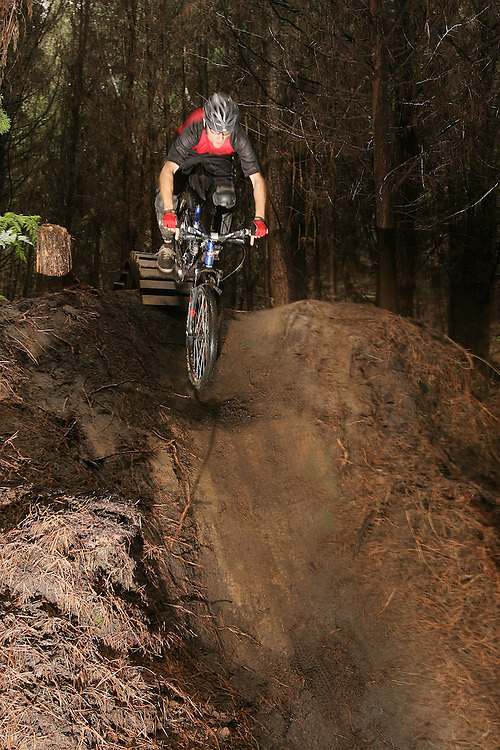 James Madelin drops into the steep exit chute on a North Shore style rollercoaster structure, on the trail 'Double Down' in the trail network of the Whakarewarewa forest (known as the Redwoods) in Rotorua, New Zealand. 26Jan07. Photo James Madelin.