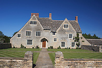 The manor house is constructed from mellow Cotswold stone with mullion windows and a steeply sloping roof