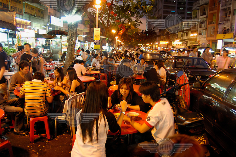 People eating and drinking at tables at a mostly Chinese night food market on Jalan Alor in the Golden Triangle.