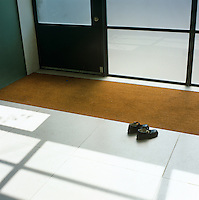 A tiny pair of child's sandals on the limestone floor before the galvanised steel and glass entrance doors to the former warehouse