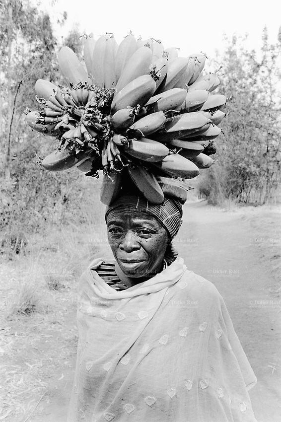 Burundi. Karuzi Province. Buhiga. An old woman walks on a dirt road and carries bananas on her head. She goes to the market to sell the bananas to customers.  © 2000 Didier Ruef