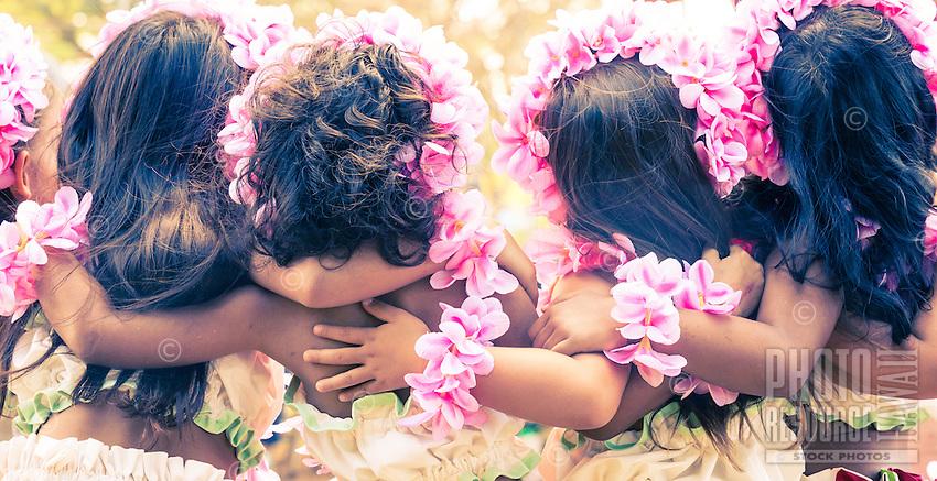 Girls with pink plumeria lei and haku head lei during a hula performance in Hale'iwa, North Shore, O'ahu.