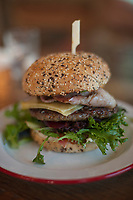"An Australian hamburger, served with ""the lot"" (in this case, bacon, lettuce, tomato, cheese, and pickled beetroot) on a seeded bun."