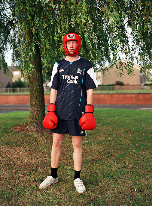 HATTERSLEY, UK - Kieran, a successful young boxer, poses for a portrait outside the local gym on the Hattersley Estate. . .The Hattersley Estate was created in the early 1960s to house residents displaced by the slum clearances of inner city Salford and Manchester and soon gained notoreity between 1963 and 1965 as the home to the Moors Murderers, Myra Hindley and Ian Brady. Lying in a relatively isolated area on the edge of the Pennines, residents today continue to wait for the investment and infrastructure promised to them decades ago. In the gap between promise and reality, a unique characted formed during years of adversity continues to thrive on the estate.