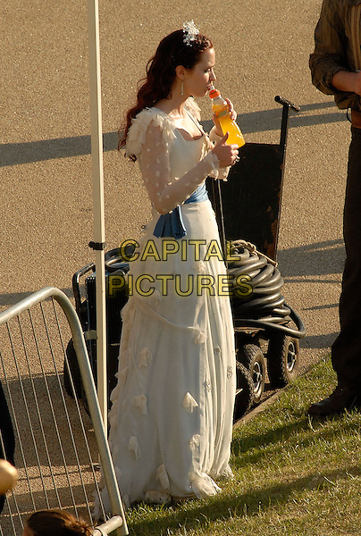 """EMILY BLUNT.On the film set of """"Gulliver's Travels"""" in Greenwich, South East London, England, UK, June 1st 2009..filmset movie on location filming full length break costume white dress drink drinking blue sash long tiara hairband .CAP/IA.©Ian Allis/Capital Pictures"""