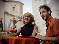 A young Italian couple enoys wine while sitting outdoors at a Cafe in Spoleto.