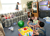 Erin Porch of Douglassville, Pa. holds her baby daughter Audrey 11 months, while her daughter Kaila 8 listens to music on the couch, son Trevor 5 jumps on the couch and Aidan 3, builds blocks in their home on Friday September 23, 2004. Erin had an online business, The Sling Lady, until the demands of her homelife made her close her business after 5 years of service.  Newhouse News Service photo by jane therese